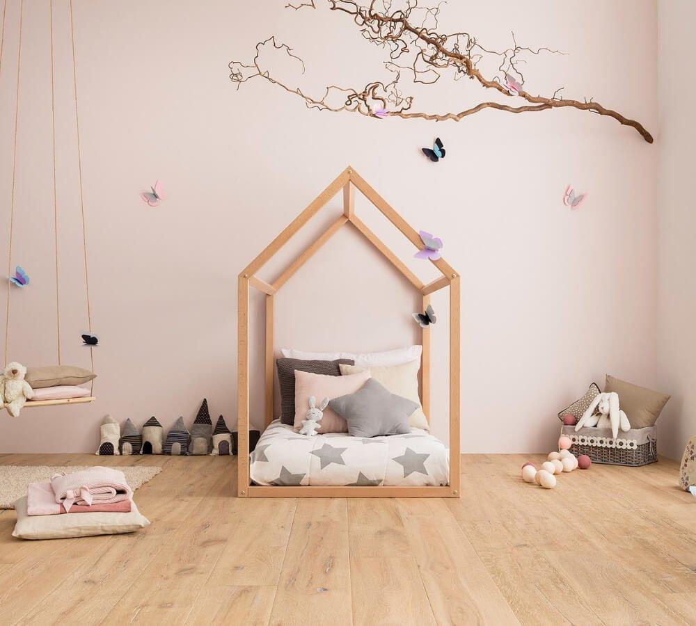 Lettino Montessori a forma di casetta allestito in modo romantico e decorato con stelle e farfalle
