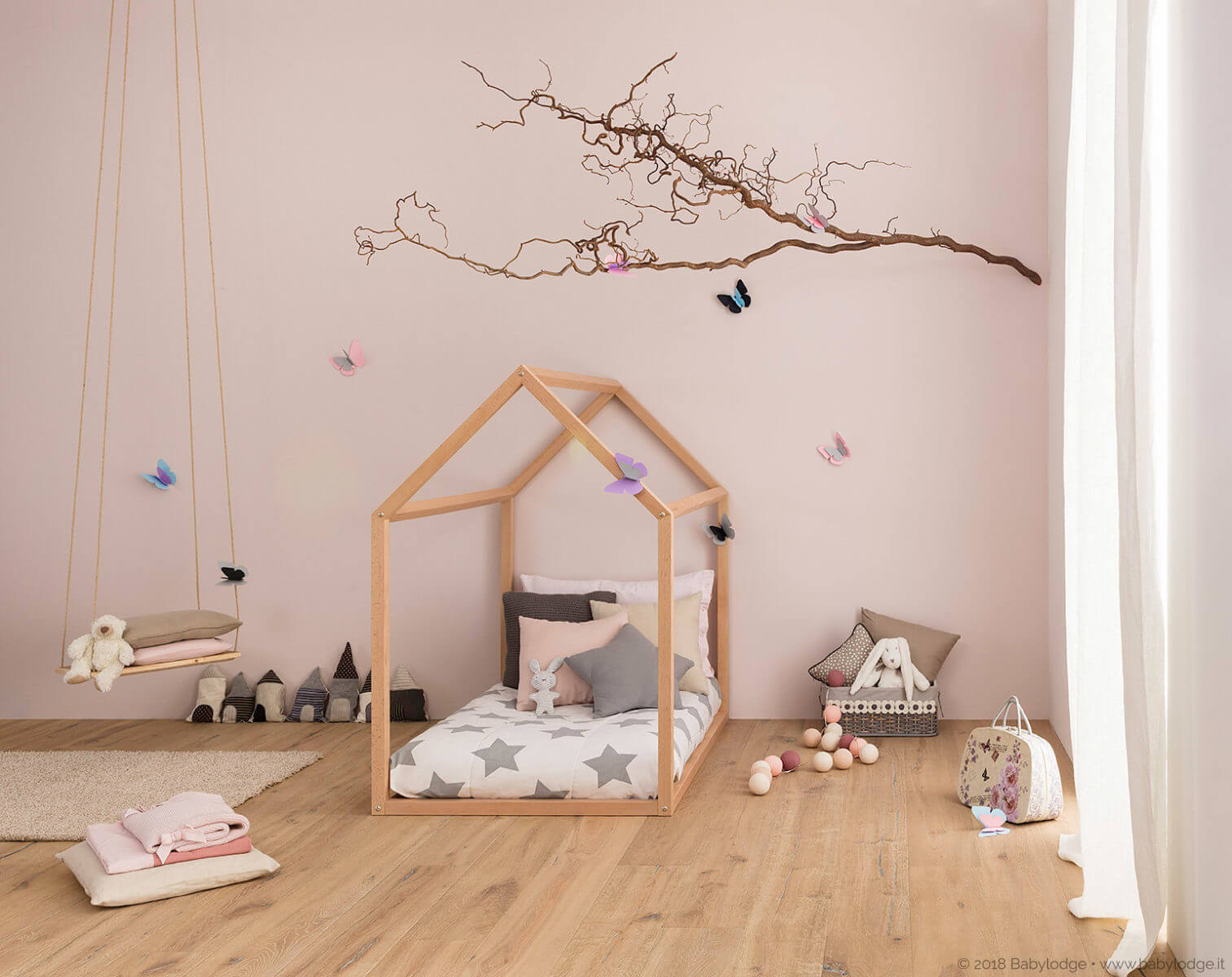 Lettino Montessori a forma di casetta allestito in cameretta romantica decorata con stelle e farfalle