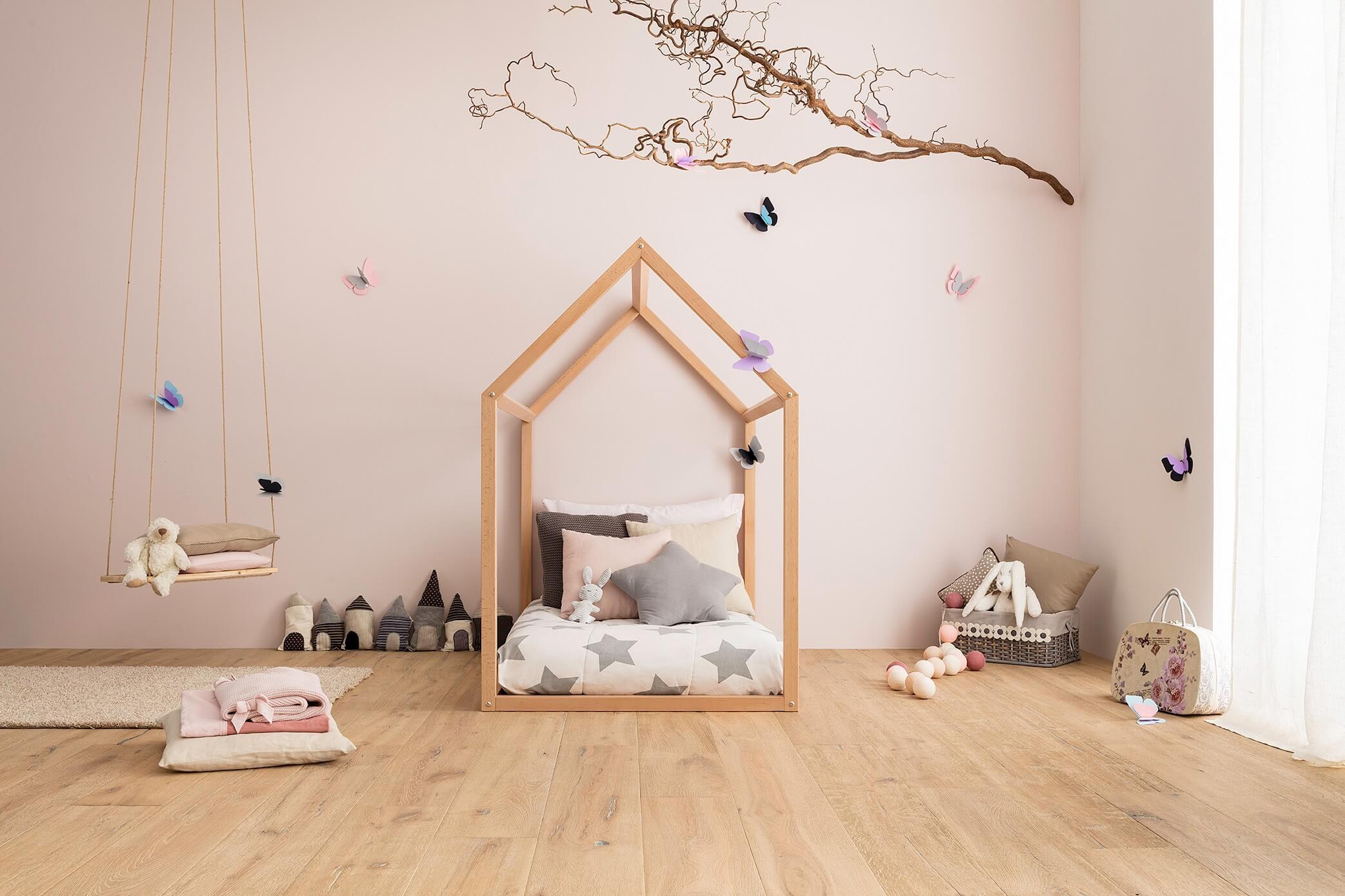 Lettino Montessori a forma di casetta allestito in cameretta rosa decorata con stelle e farfalle