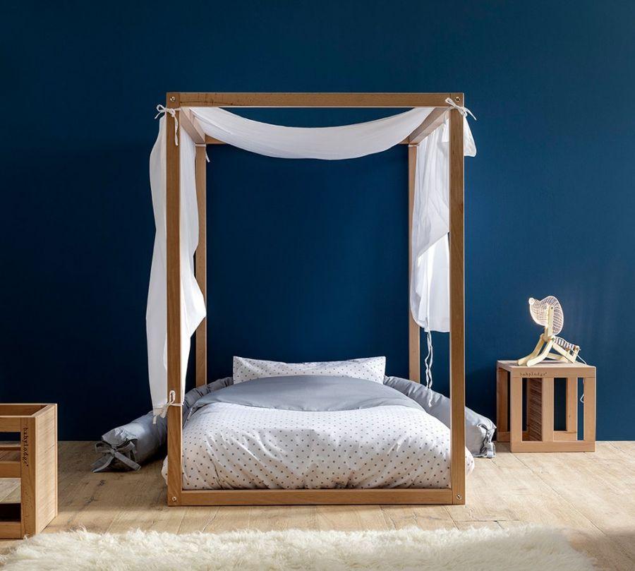 Lettino Montessori a baldacchino in cameretta con parete blu e comodino di legno, Babylodge