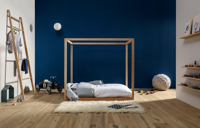 Lettino Montessori a baldacchino in cameretta con parete blu scuro